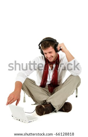 Handsome young caucasian man with headphones  and laptop, sitting cross-legged and listening music from the internet. Studio shot. White background.
