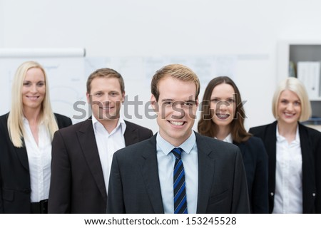 Handsome young Caucasian manager smiling with a happy team made of three women and a man, behind him - stock photo