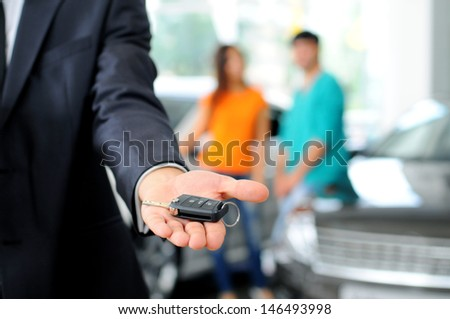 Handsome young classic car salesman standing at the dealership holding a key for a car - stock photo