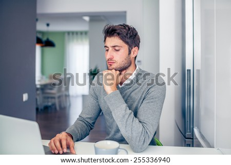 Handsome young concentrated businessman working from home with a laptop with his coffee mug - stock photo