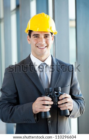 handsome young construction manager with binoculars - stock photo