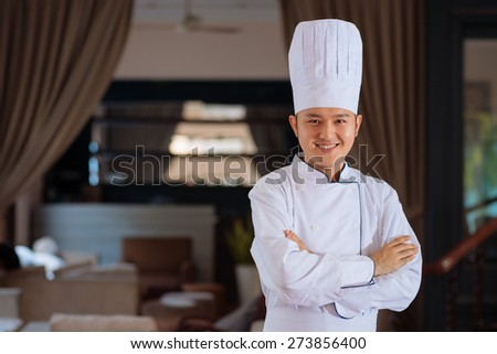 Handsome young cook in a restaurant smiling and looking at the camera - stock photo