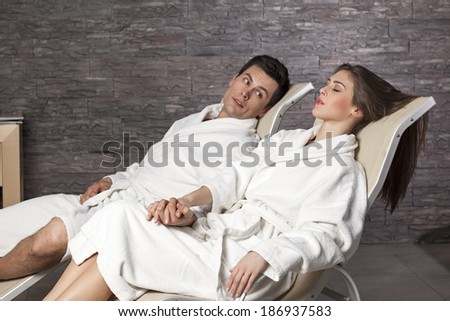 Handsome young couple in bathrobe relaxing in spa center