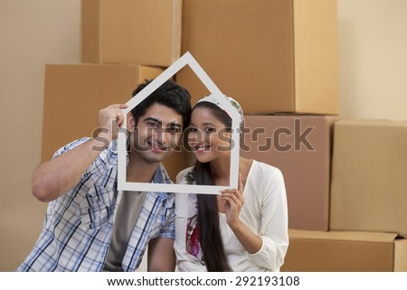 Handsome young couple smiling while looking through house shaped frame - stock photo