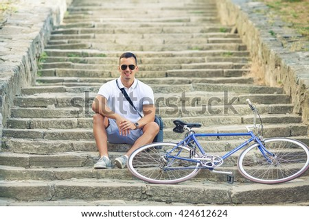 Handsome young cyclists resting on the steps of the fortress in the old town with his bicycle beside him - stock photo
