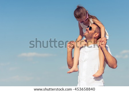 Handsome young dad and his cute little daughter looking at each other and smiling. Girl is sitting on her father's shoulders, sky on the background - stock photo