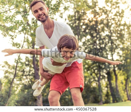 Handsome young dad and his cute little son are looking camera and smiling while playing in park. Father is holding his son in arms, boy is imitating an airplane - stock photo