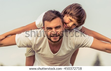 Handsome young dad and his cute little son are looking camera, smiling and imitating an airplane while playing in park. Son is on father's back - stock photo