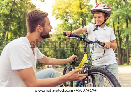 Handsome young dad and his cute little son are riding bikes in park. Both are looking at each other and smiling while father is examining his son's bicycle - stock photo