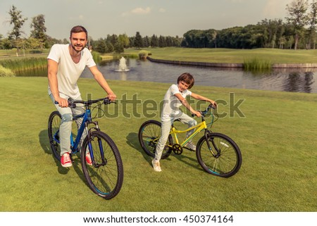 Handsome young dad and his cute little son in casual clothes are looking at camera and smiling while riding bikes in park near the pond