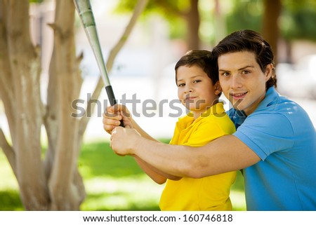 Handsome young dad teaching how to swing a bat to his kid at a park - stock photo