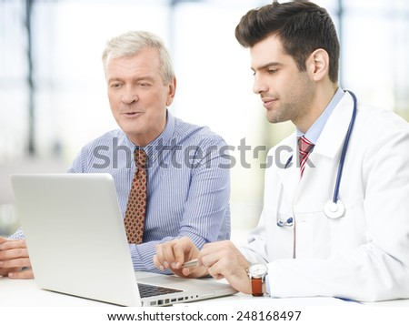 Handsome young doctor explaining results to a senior patient.