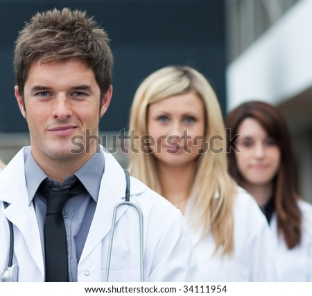 Handsome young doctor leading his team and looking at the camera - stock photo