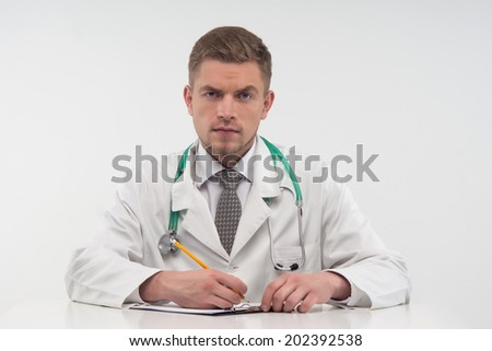 Handsome young doctor, sitting at the table and writing intently letter of recommendation for one of his colleagues. Isolated on the white background