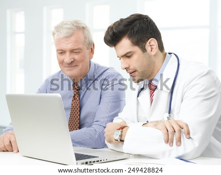 Handsome young doctor sitting in front of computer and consulting with old patient.