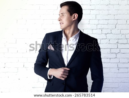Handsome young elegant man posing in fashionable suit. - stock photo