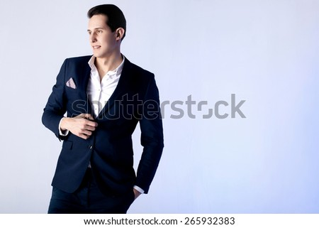 Handsome young elegant man posing in fashionable suit.