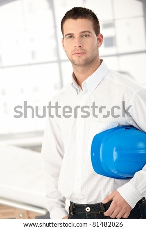 Handsome young engineer standing in bright office.? - stock photo