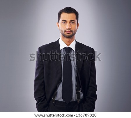Handsome young executive in business suit standing in a studio - stock photo