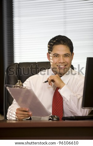 Handsome young executive male sitting at his desk. - stock photo