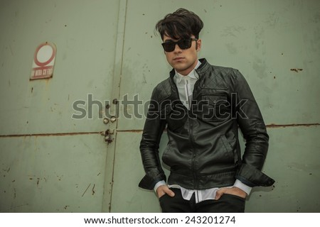 Handsome young fashion man leaning on a green metal door with his hands in pockets. - stock photo