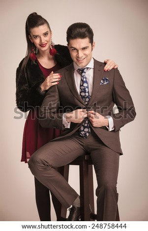 Handsome young fashion man sitting on a stool while closing his jacket. His girlfriend is standing behind him with her hands on his shoulders. - stock photo