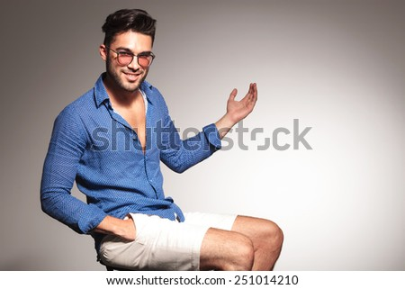 Handsome young fashion man sitting on a stool with his hand in pocket, presenting something to his left. - stock photo