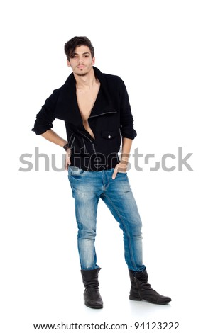 Handsome young fashion model standing and wearing jeans, boots and a black jacket. Isolated on white background. Studio vertical image.