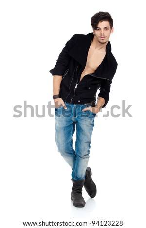 Handsome young fashion model standing with hands in pockets, wearing jeans, boots and a black jacket. Isolated on white background. Studio vertical image.