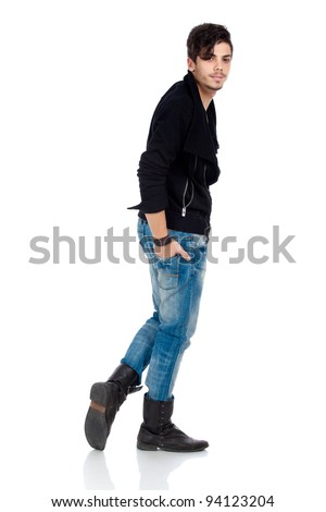 Handsome young fashion model wearing jeans, boots and a black jacket. Isolated on white background. Studio vertical image. - stock photo