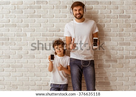 Handsome young father and his cute little son showing smart phones, listening to music, looking in camera and smiling. Both in white t-shirts and jeans, standing against white brick wall. - stock photo
