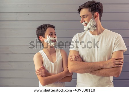 Handsome young father and his teenage son with shaving foam on their faces are looking each other and smiling, standing cross-armed against gray wall - stock photo