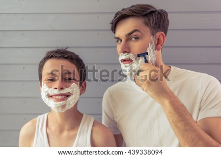 Handsome young father and his teenage son with shaving foam on their faces are shaving and looking at camera, against gray wall. Boy is smiling - stock photo