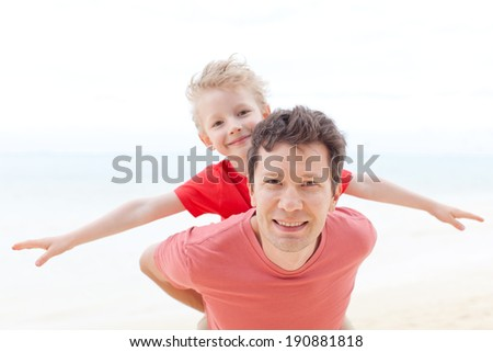 handsome young father giving his little son piggyback ride, son playing a plane, having fun day together - stock photo