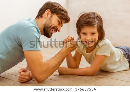Handsome young father in casual clothes and his cute little son competing in arm wrestling while lying on a wooden floor in the room - stock photo