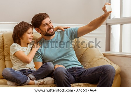 Handsome young father in casual clothes and his cute little son making a photo using a smart phone while sitting on a sofa in the room - stock photo