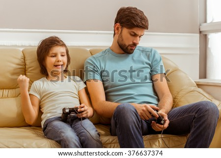 Handsome young father in casual clothes and his cute little son playing console games while sitting on a sofa in the room. A little boy won. - stock photo