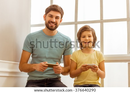 Handsome young father in casual clothes and his cute little son using smart phones, looking in camera and smiling while sitting near the window - stock photo