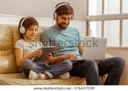 Handsome young father in casual clothes using a laptop and his cute little son using a tablet while sitting on a sofa in the room. Both in headphones. - stock photo