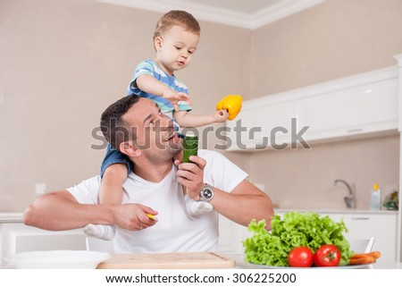 Handsome young father is sitting at the table and holding his son on his shoulders. He is looking at his child and smiling. The boy is holding a pepper and taking a cucumber with interest - stock photo