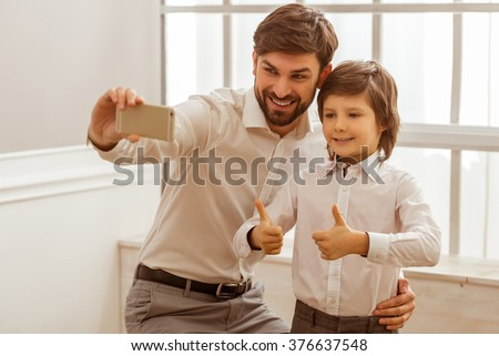 Handsome young father making a photo with his cute little son. A little boy showing OK sign. Both in white classical shirts smiling. - stock photo