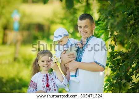 handsome young father with children on nature - stock photo