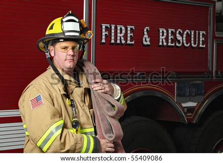 handsome young fireman holding fire hose in uniform in front of firetruck - stock photo