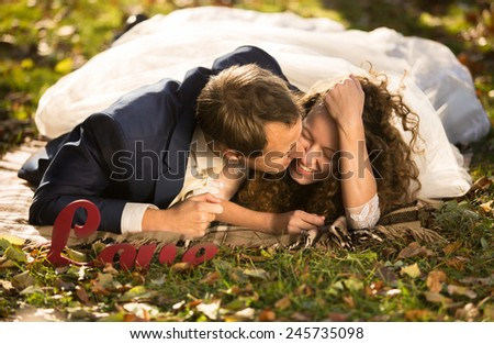 Handsome young groom kissing beautiful bride in cheek lying on grass at park - stock photo