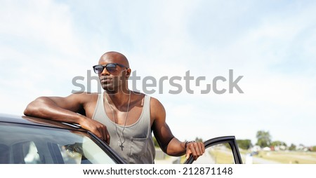 Handsome young guy leaning on car. African male model wearing sunglasses standing by his car looking away with door open outdoors. Stylish driver. - stock photo