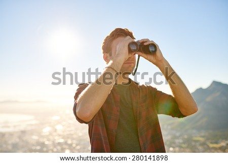 Handsome young guy looking through his binoculars at the horizon with bright sun flare  - stock photo