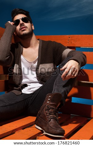 handsome young guy sitting and posing in casual clothes - stock photo