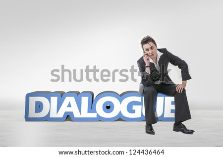 Handsome young guy using a mobile phone and sitting on 3d text