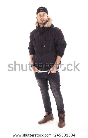 Handsome young guy wearing jacket and black cap with her hands on pockets using gold glasses