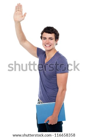 Handsome young guy with a notebook in hand putting his right hand up isolated over white - stock photo